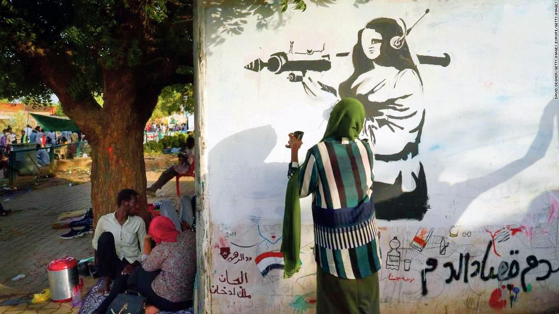 Soudan: une femme réalise une peinture murale