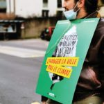 Homme à velo portant une pancarte politique de solidaritéS