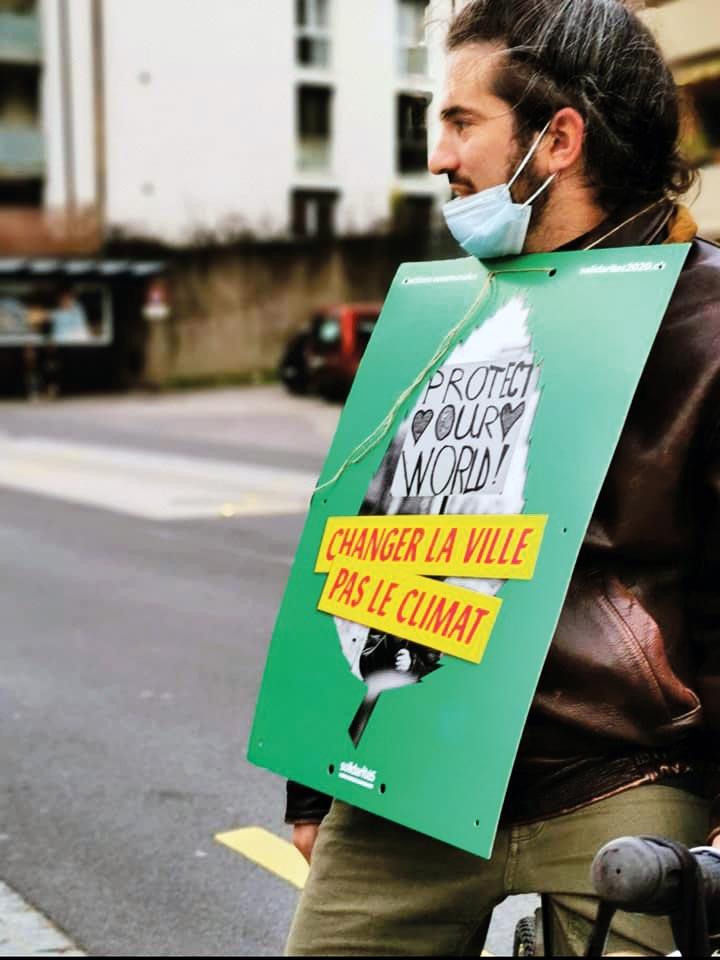 homme-à-velo-portant-pancarte-politique-de-solidaritéS