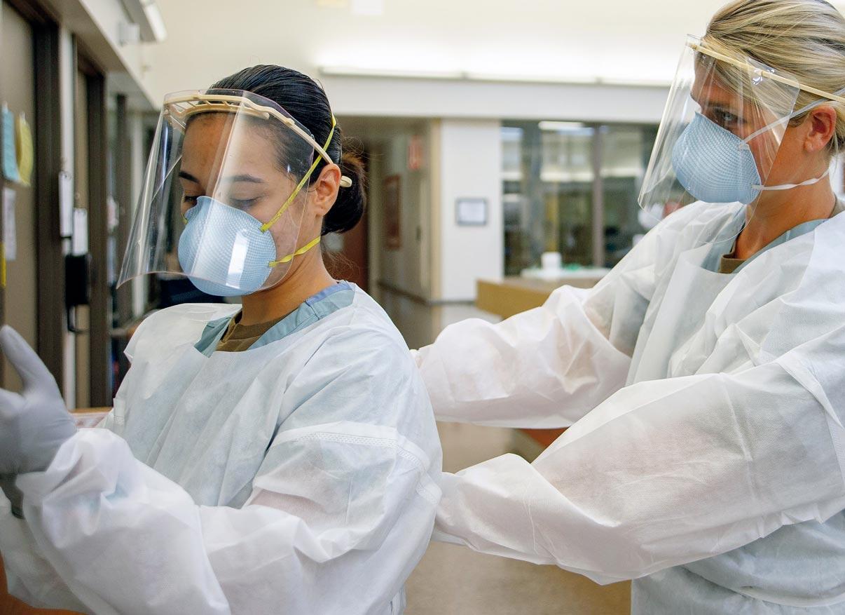 Une infirmière aide sa collègue à enfiler sa combinaison