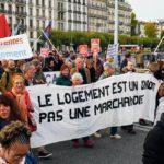 """Manifestants portant une banderole """"Le logement est un droit pas une marchandise"""""""