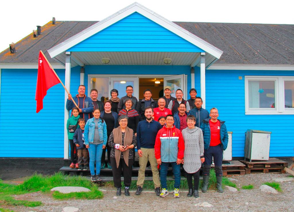 Militantes du parti Inuit Ataqatigiit du Groenland devant une habitation typique