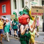 """Femme avec un masque de tomate portant un panneau """"pesticides = écocide"""""""