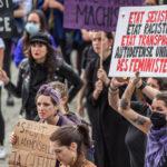 """Manifestante portant un panneau """"Etat sexiste, Etat raciste, Etat transphobe"""" lors de la Grève féministe du 14 juin 2020 à Lausanne"""