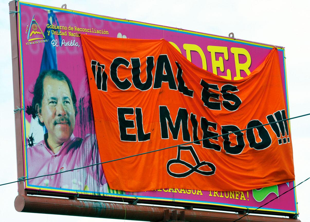 Panneau électoral représentant Daniel Ortega recouvert par des protestataires