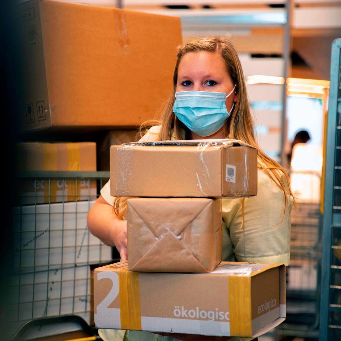 Une employée de la Poste suisse tient des colis