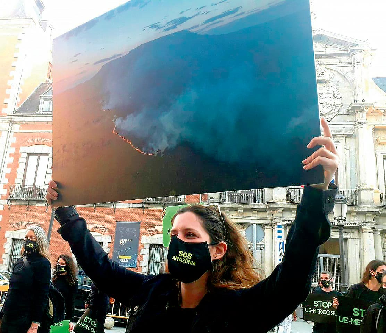 Manifestante brandissant une photo de l'Amazonie en feu