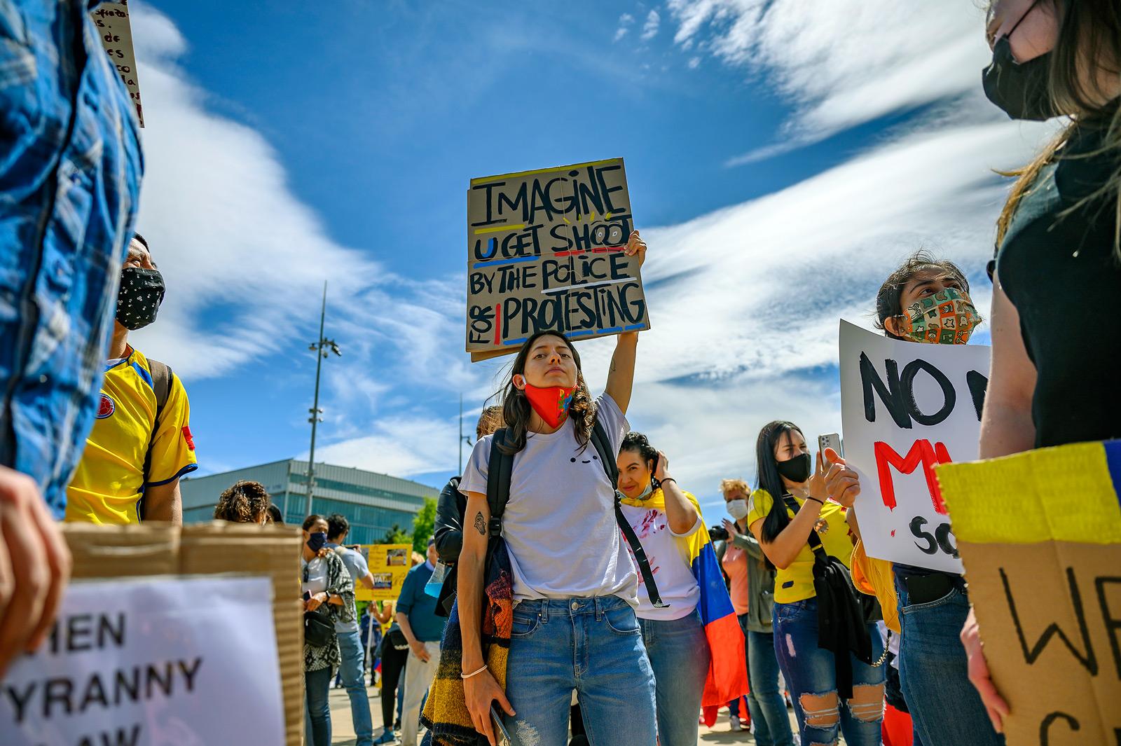 """Une manifestante tient une pancarte """"Imagine U get shot by the police for protesting"""" lors de la manifesation de soutien au peuple colombien, Genève, 8 mai 2021"""