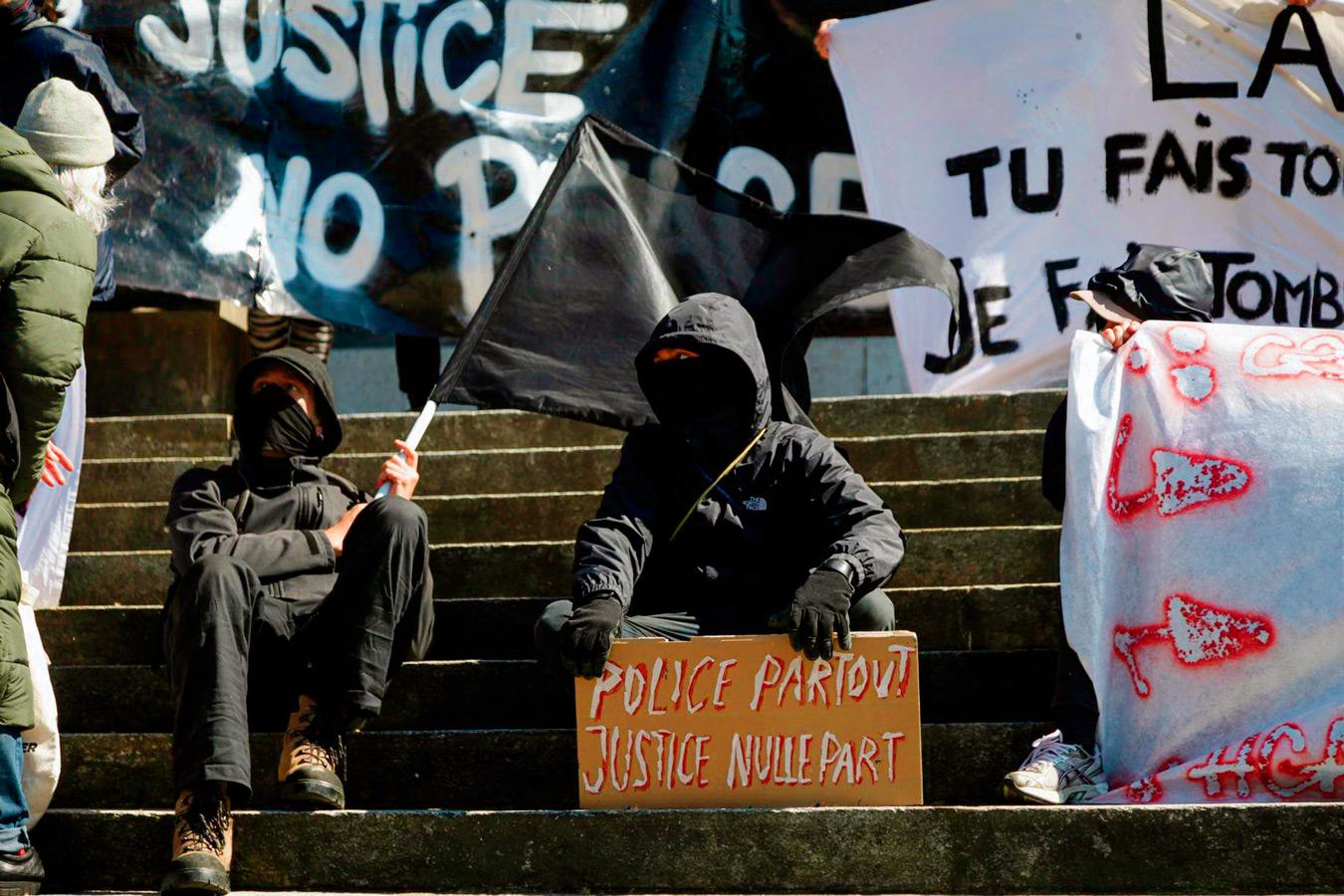 """Deux manifestants avec une pancarte """"Police partout, justice nulle part"""" lors de la manifestation contre la répression policière, Lausanne, avril 2021"""