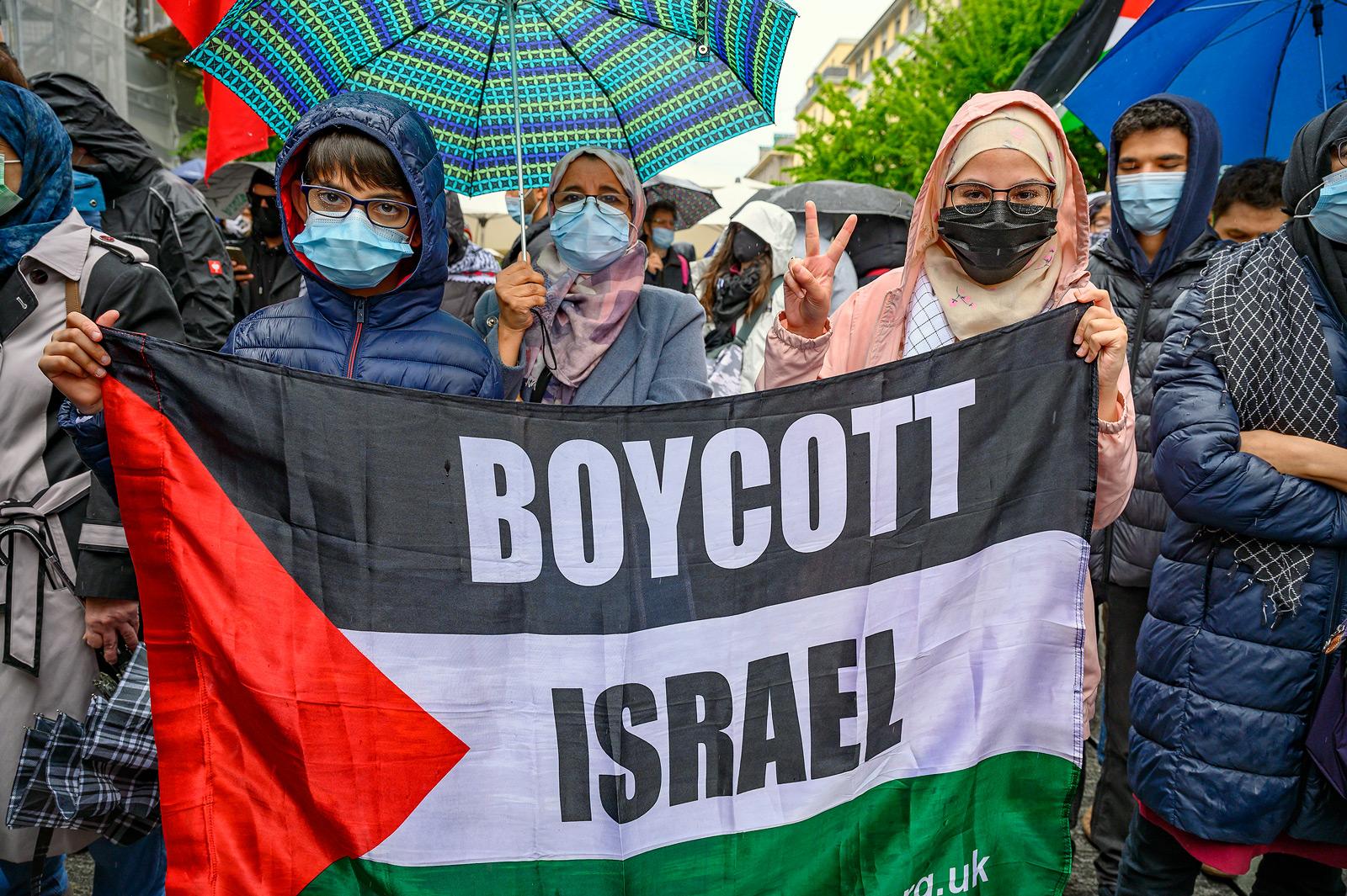 """Deux femmes tiennent une banderole """"Boycott Israël"""" lors de la manifestaiotn du 15 mai 2021 à Genève"""