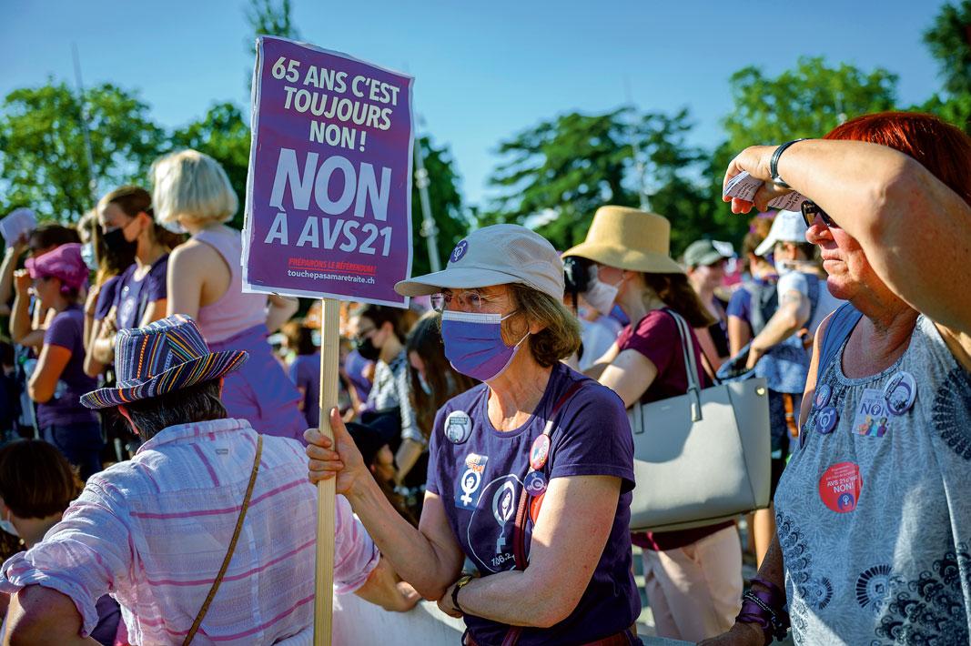 Une manifestante porte une pancarte: Non à AVS21