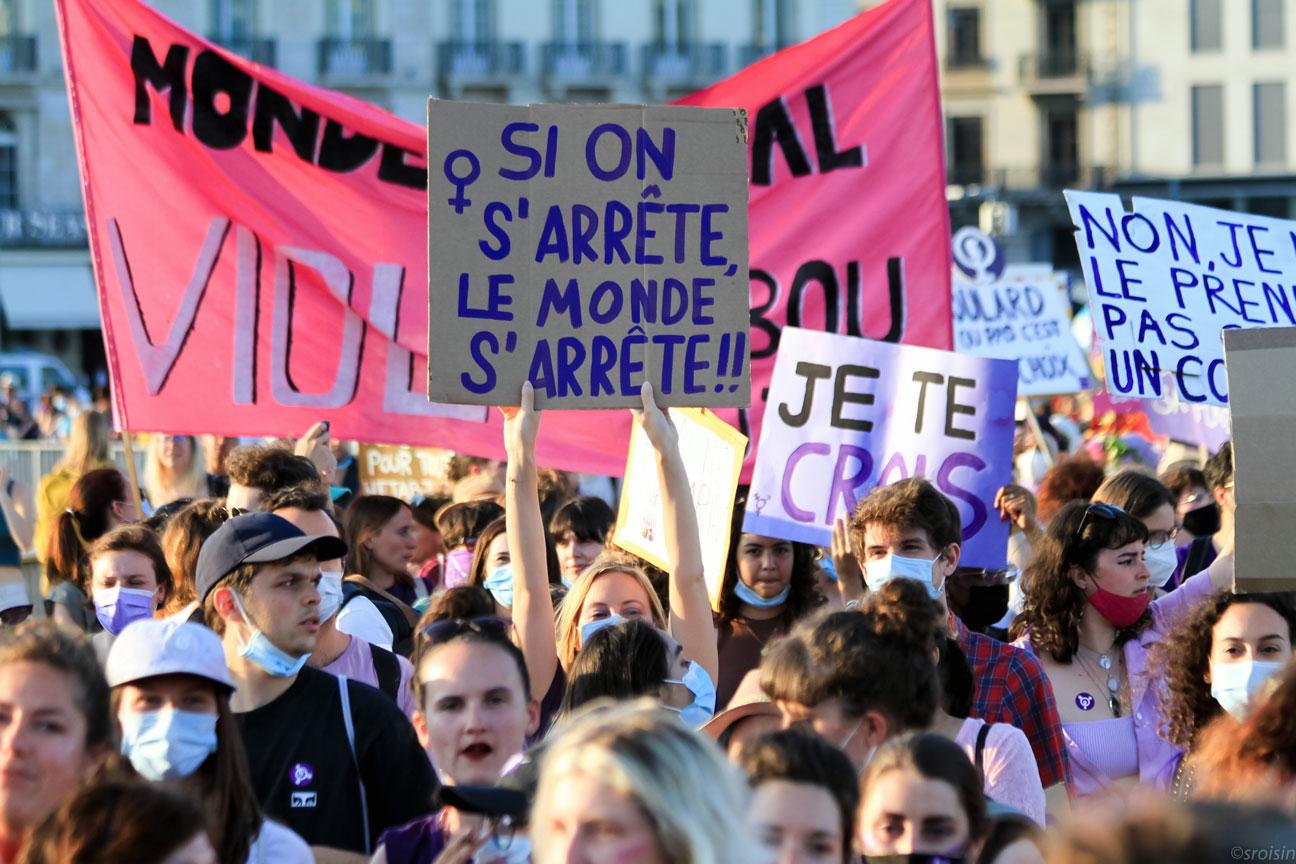 """Une manifestante féministe porte une pancarte """"Si on s'arrête, le monde s'arrêtre"""""""