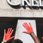 Un manifestant avec les mains peintes en rouge devant le Credit Suisse