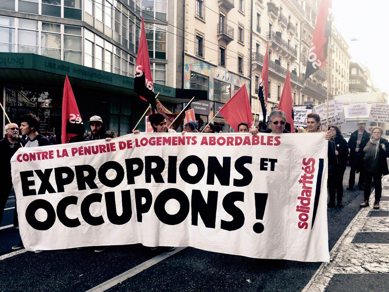 """Des manifestants portent une banderole """"Contre la pénurie de logements abordables, exproprions et occupons!"""""""