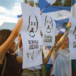 Des manifestantes portent des pancartes avec le portrait de Daniel Ortega