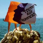 """Deux femmes tiennent un drapeau """"toutes aux frontières"""" au bord de la Méditerrannée"""
