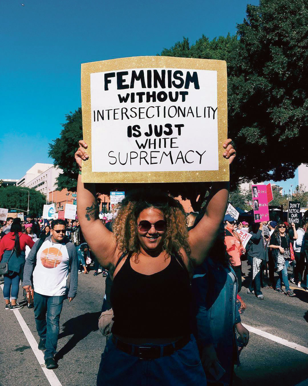 """Une manifestante féministe tient une banderole """"Feminism without intersectionality is just white supremacy"""""""