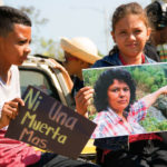 Deux enfants portent un portrait de Berta Caceres lors d'un rassemblement