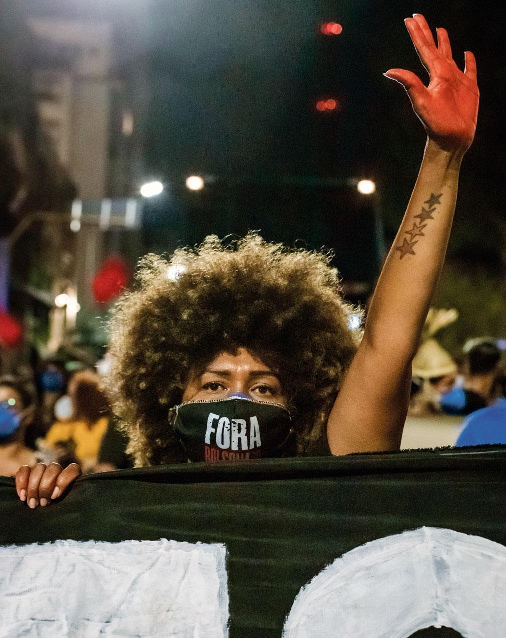 Une manifestante lève une main peinte en rouge pour protester contre le gouvernement Bolsonaro au Brésil
