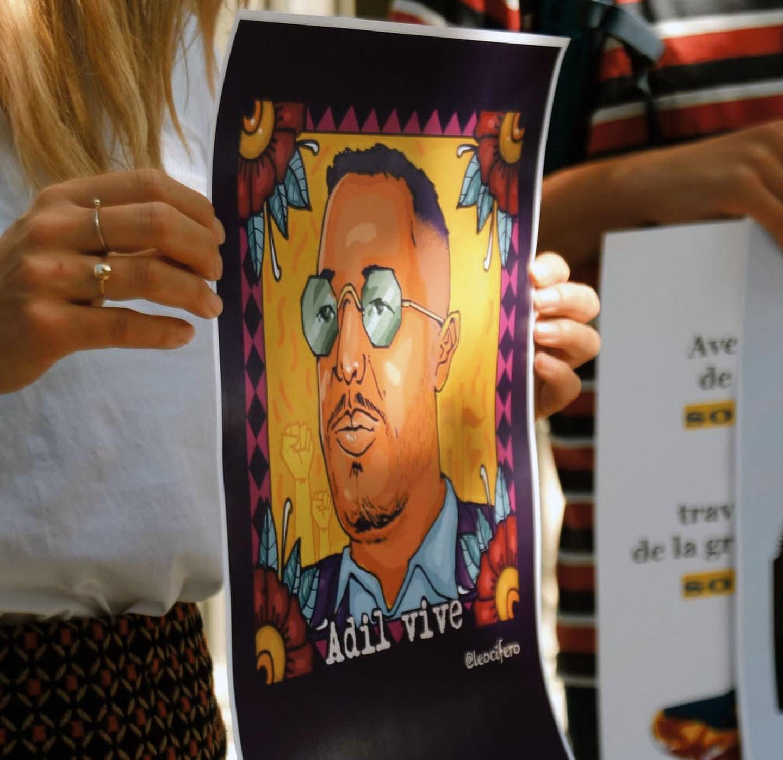 Une manifestante tient un portrait d'Adil Belakhdim, Lausanne