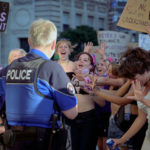 Un policier et des manifestantes de la grève féministe