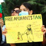 Une manifestante porte un panneau Free Afghanistan