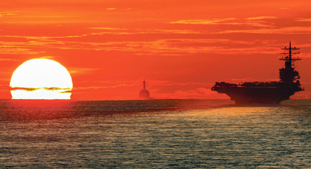 Porte avion USS Ronald Reagan devant un soleil couchant