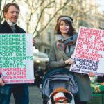 Deux personnes tiennent des pancartes pour les transports publics gratuits et de meilleures conditions de travail