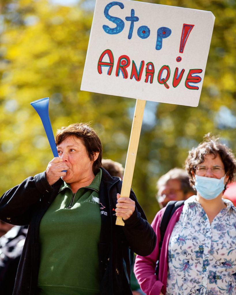 """Une employée de la Ville de Genève tient une pancarte """"Stop arnaque"""""""