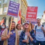 Deux manifestantes portent des pancartes contre AVS21