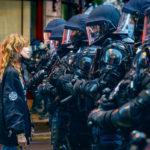 Une manifestante interpelle des policiers lourdement armés