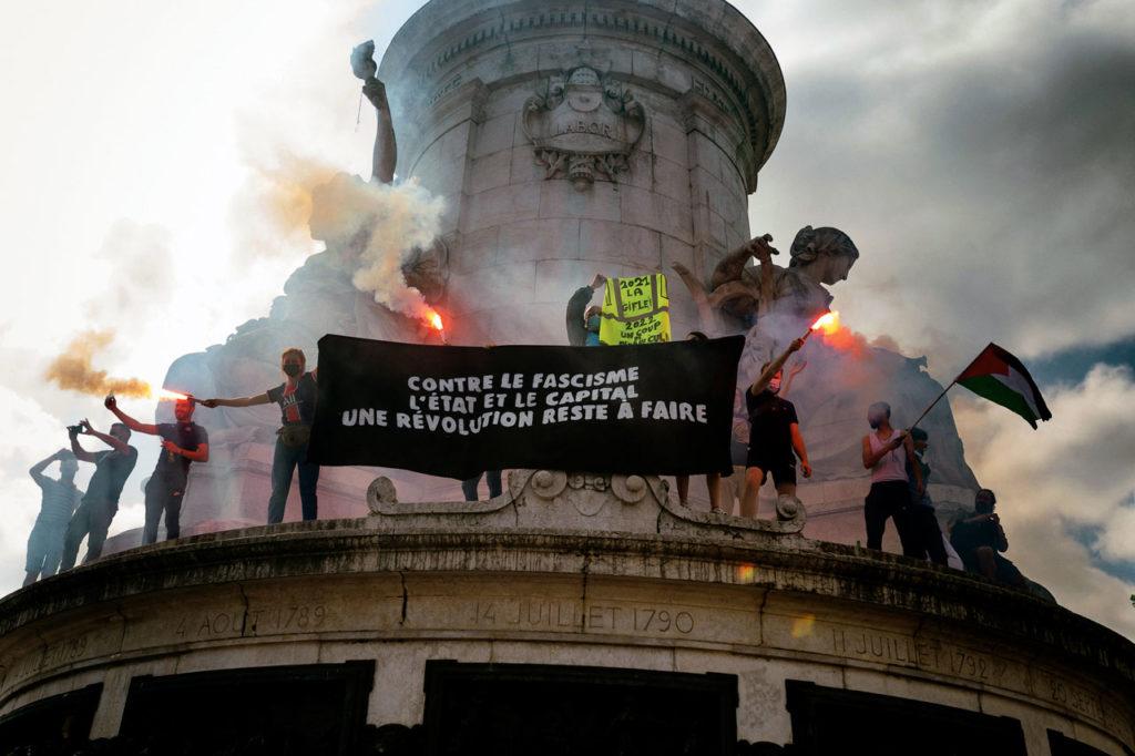 Des manifestants à Paris portent une banderole Contre le fascisme, l'Etat et le capital.
