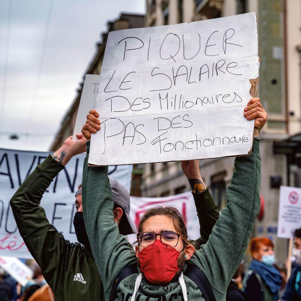 """Un manifestant porte une pancarte """"Piquer le salaire des millionaires pas des fonctionnaires"""""""