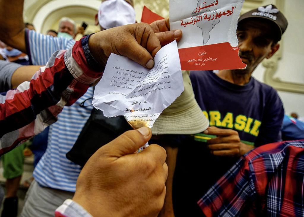 Un manifestant tunisien pro Kais Saied brûle la Constitution